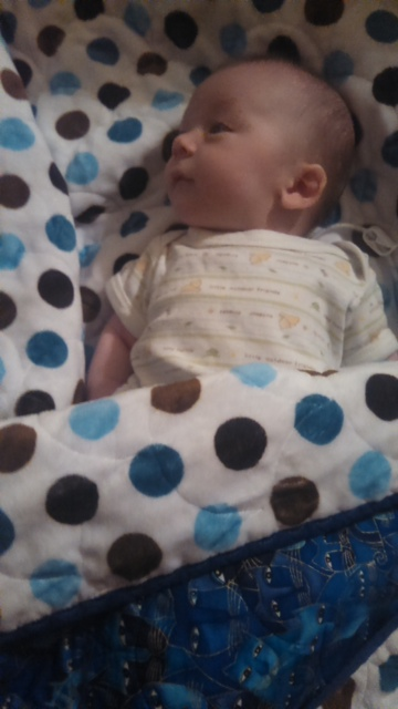 Newborn Aidan with his polka-dot minky quilt