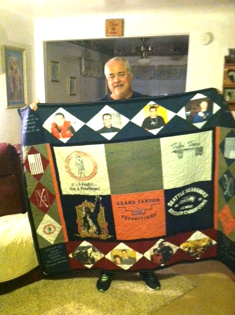 Shannon's Dad displaying the quilt made from his t-shirts.