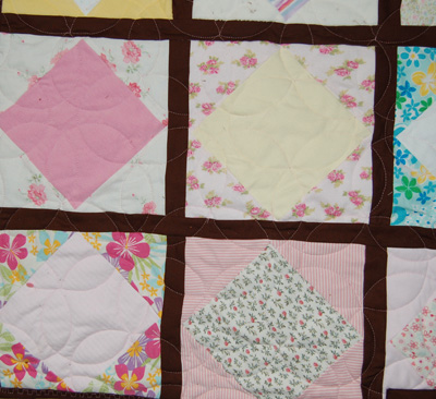 Detail of quilt made from scraps of baby clothes