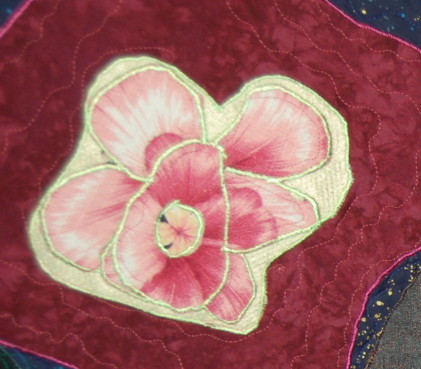 Fabric lily made to represent a cat's eye nebula in quasar quilt