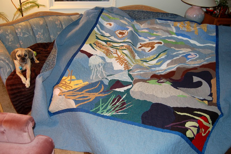 Bereavement quilt seascape displayed on sofa with Duncan