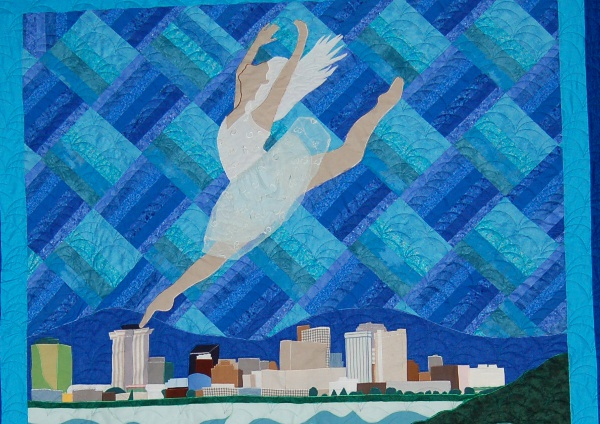 Top portion of Lady Dancing above the skyline of New Orleans