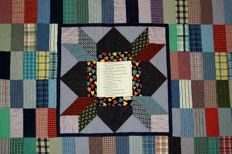 Center of bereavement quilt made of ties and a print of her favorite poem