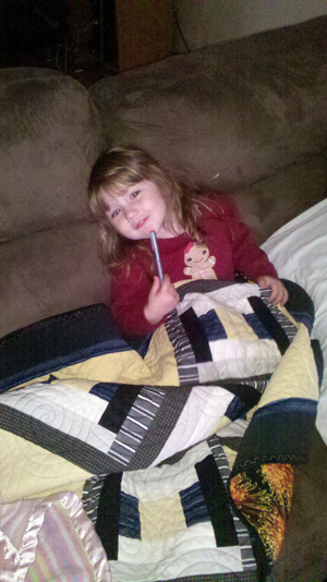Bailey holding her small bereavement quilt made from her granddaddy's clothes
