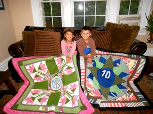 Collin and Mackie displaying their bereavement quilts made from mom's clothing